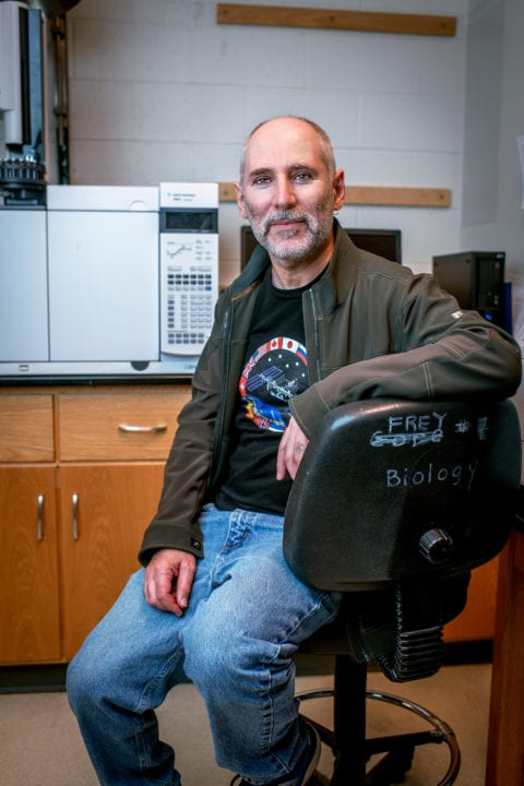 Biology professor Eric Gilbert seated in his lab.