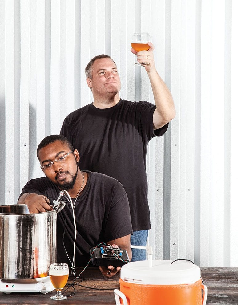 Partners in beer: Michael Weeks enjoys a brew while D'juan Blue inspects his equipment.