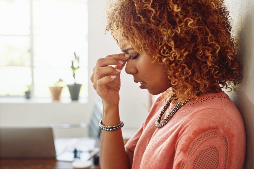 Woman showing signs of stress in an office environment