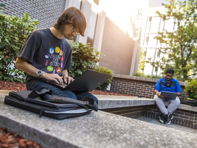 College student works on a laptop outdoors
