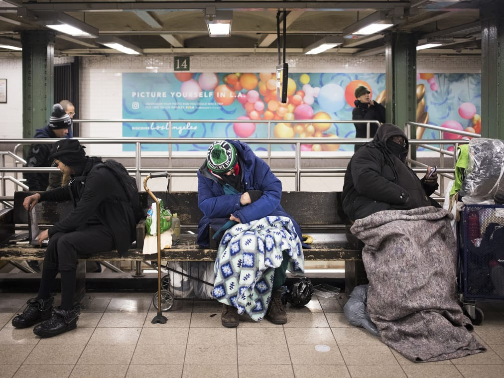 Three homeless people sleep in a train station
