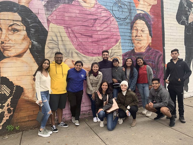 Latino Leadership Pipeline scholars from Perimeter College and a staff member pose in front of a mural during an outing. Standing, from left: Belen Valle, Maikel Atez Adames, Ana Rodriguez-Garcia, Libia Jimenez (Latinx Student Services and Outreach, assistant director), Korben Castañeda, Lisset Vargas, Karla Negrete, Betzahida Escalante and Daniel Garcia. Kneeling, from left: Anni Collantes, Janette Anguiano and Jose Sandoval.