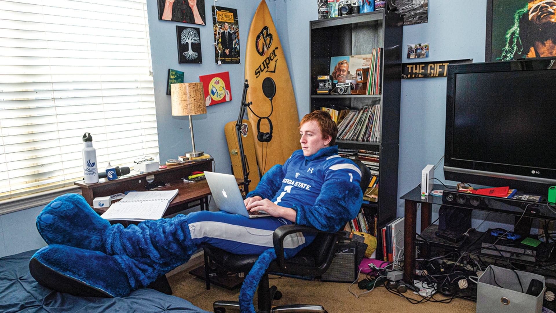 Austin Birchell (B.A. '20) sitting in his room with Pounce suit on.