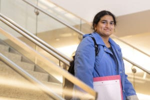 Nitheyaa Shree, Georgia State's first Marshall Scholar, poses on the stairs in the university library.