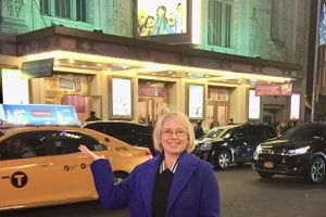"Natasha Davison (B.A. '93), co-producer of the musical ""The Prom,"" outside the Longacre Theatre on opening night."