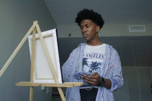 Isaiah Richburg stands at an easel with a paintbrush and palatte in his hands.