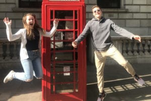 Honors students jump for joy in the sunshine outside a red London phone booth