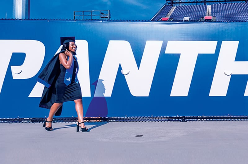 a photo of an African-American graduate walking outside of the Georgia State stadium