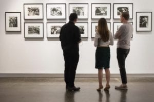Three observers take in an art exhibition in the Welch Galleries
